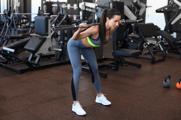 Gespierde vrouw trainen in de sportschool doen oefeningen met barbell op biceps.