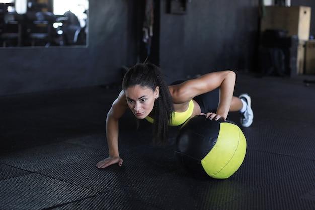 Gespierde vrouw traint met medicijnbal in de sportschool.