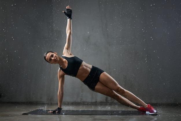 Gespierde vrouw zij plank oefening beoefenen