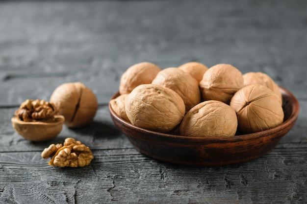 Gespleten walnoot met een klei kom vol noten op een donkere rustieke tafel