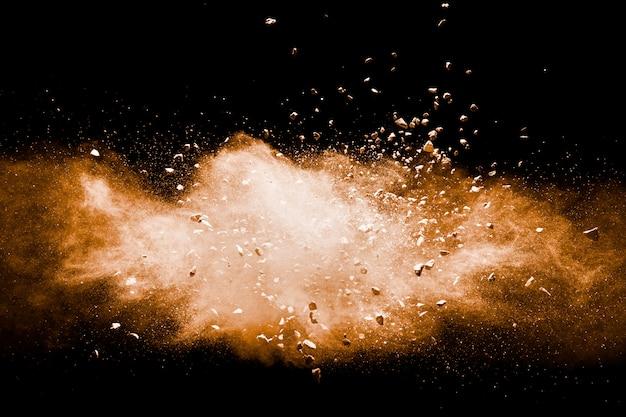 Gesplitst puin van steen die met oranje poeder tegen zwarte achtergrond exploderen.