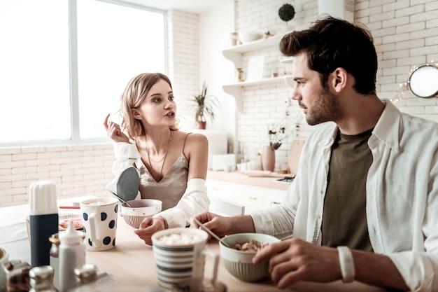 Gesprek. bebaarde knappe positieve man in een wit overhemd op zoek attent tijdens een gesprek met zijn vrouw