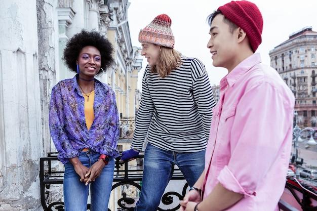 Gesprek op balkon. drie stijlvolle jonge ontwerpers die zich goed voelen met een gesprek op het balkon