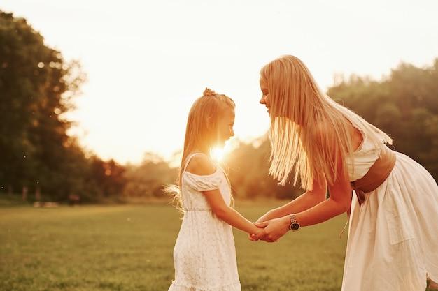 Gesprek voeren. moeder en dochter genieten samen van het weekend door buiten in het veld te wandelen. prachtige natuur.