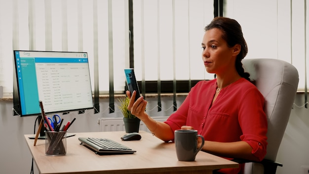 Gesprek voeren op de webcam met behulp van de telefoon in de kantoorruimte. freelancer werkt met zakelijk team op afstand dat chatten met online conferentie bespreekt, webinar met internettechnologie