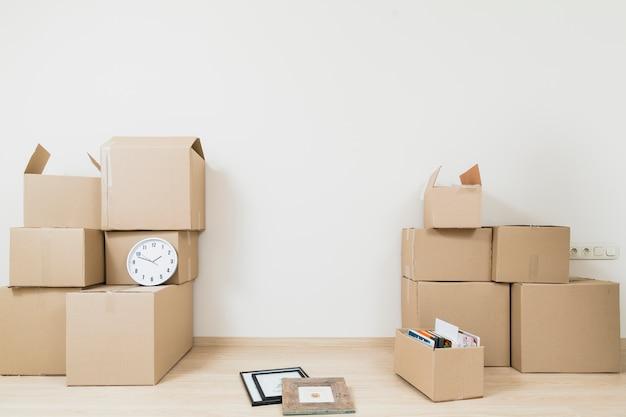 Gestapeld van bewegende kartonnen dozen met klok en fotolijst tegen witte muur