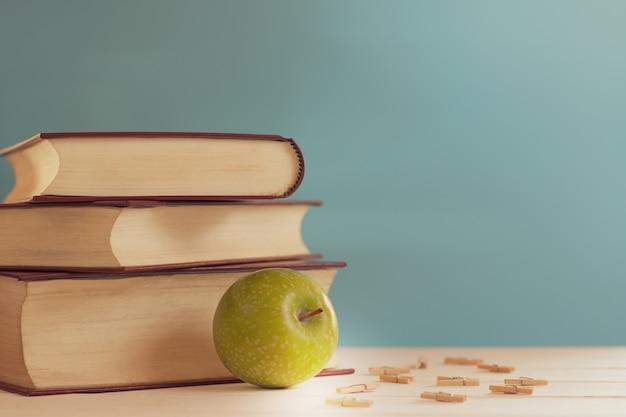 Gestapeld van boek en groene appel op de tafel voor achtergrond.