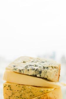 Gestapeld van driehoekige kaas plakjes tegen een witte achtergrond