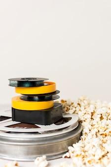 Gestapeld van filmhaspels met popcorns tegen witte achtergrond
