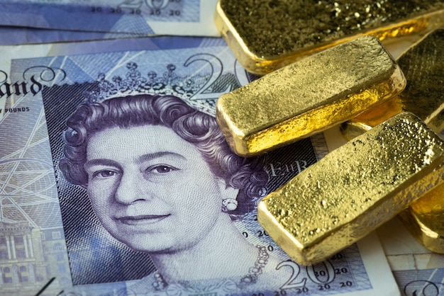 Gestapeld van goudstaaf op bankbiljet, gbp of pond met goudstaaf