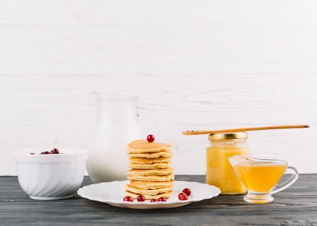 Gestapeld van kleine pannekoeken met rode aalbesbessen en citroengestremde melk tegen witte muur