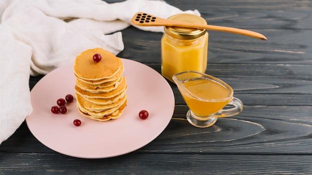 Gestapeld van pannekoeken en rode aalbesbessen met citroengestremde melk op houten achtergrond