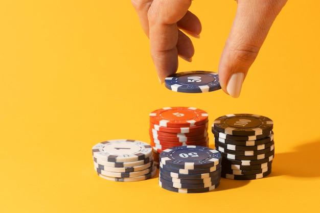 Gestapelde casinofiches op gele achtergrond