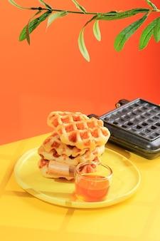 Gestapelde croissantwafel in gele lijst en oranje achtergrond. croffle is viral cake uit zuid-korea. concept pop color food, kopieer ruimte voor tekst