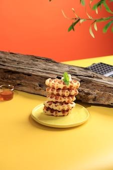 Gestapelde croissantwafel in gele lijst en oranje achtergrond. croffle is viral cake uit zuid-korea. concept pop color food