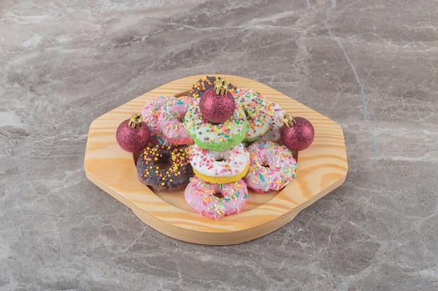 Gestapelde donuts en kerstballen op een houten schotel op marmeren oppervlak