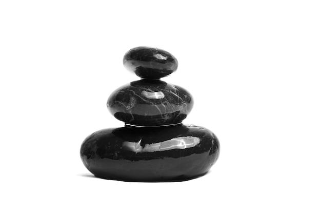 Gestapelde gladde zwarte stenen. zee kiezelsteen. in evenwicht brengende natte kiezelstenen die op witte achtergrond worden geïsoleerd