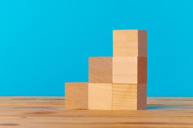 Gestapelde houten blokken op houten bureau tegen blauwe achtergrond