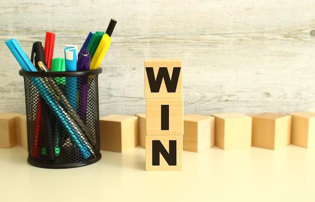 Gestapelde houten kubussen met letters win op een witte werktafel op een gestructureerde grijze achtergrond.