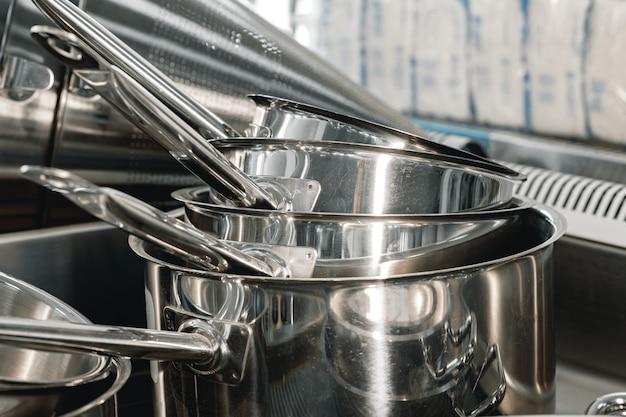 Gestapelde industriële metalen kookpotten op professionele keuken close-up