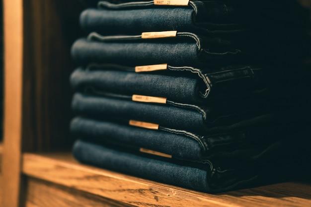 Gestapelde jeans met meerdere tailleformaten op planken of kasten en selectieve focus.