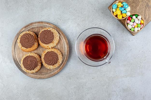 Gestapelde koekjes en twee kommen snoep op houten planken rond een kopje thee op marmeren oppervlak.