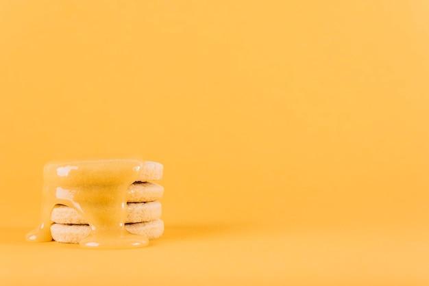 Gestapelde koekjes met citroengestremde melk op gele achtergrond