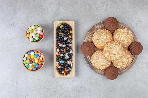 Gestapelde koekjes op een houten bord naast houten dienblad en schalen met snoep op marmeren oppervlak.