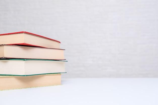 Gestapelde moderne hardback boeken op een witte tafel met kopie ruimte.