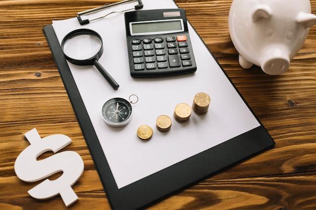 Gestapelde munten; kompas; vergrootglas en rekenmachine op klembord met dollarteken en spaarpot