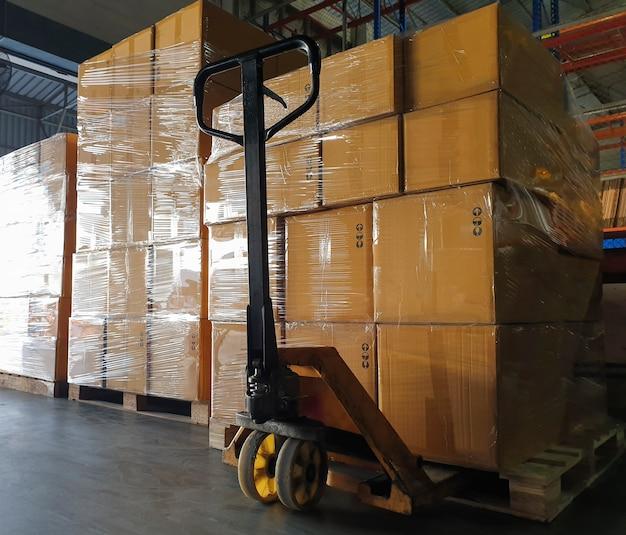 Gestapelde pakketdozen met handpallettruck in opslagmagazijn toeleveringsketen magazijn
