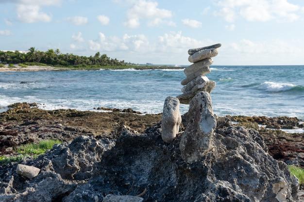 Gestapelde stenen op het caraïbische strand bij zonsondergang riviera maya-gebied