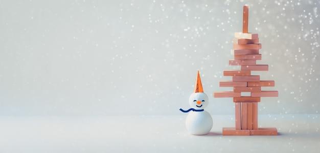 Gestapelde stokken in de vorm van een kerstboom met sneeuwpop. kerst concept