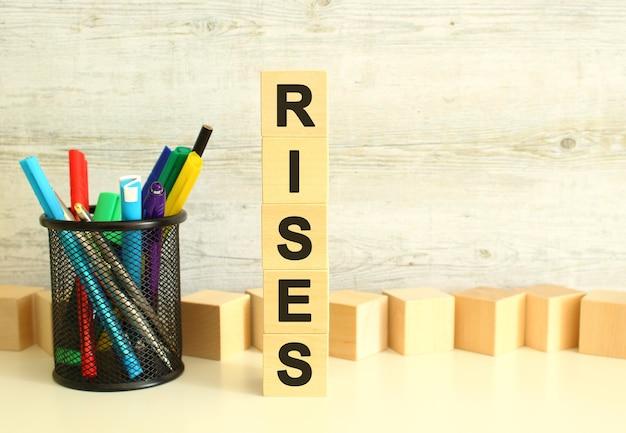 Gestapelde verticaal houten kubussen met letters in het woord rises op een witte werktafel op een gestructureerde grijze achtergrond. bedrijfsconcept