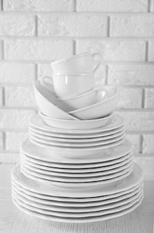 Gestapelde witte schone borden en kopjes op witte tafel
