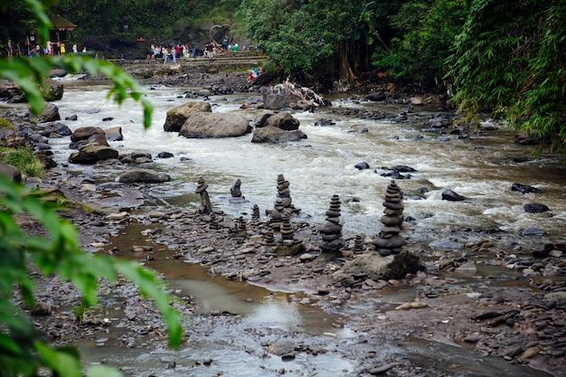 Gestapelde zenstenen bij tegenungan-waterval in bali, indonesië