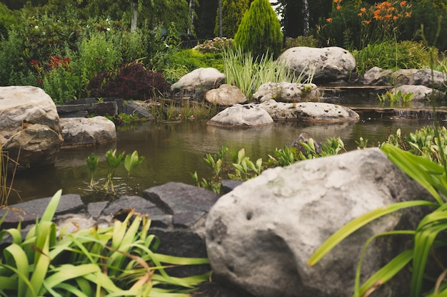 Gestemd beeld van mooie formele tuin met grote rotsen en snelle stroom