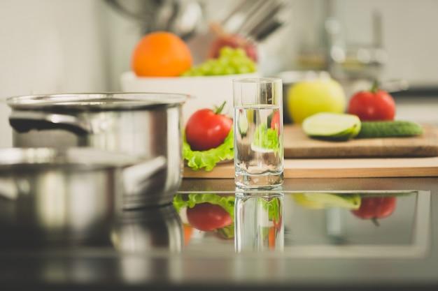 Gestemd beeld van verse groenten die naast elektrisch fornuis op moderne keuken liggen