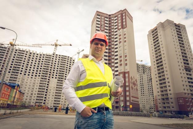 Gestemd portret van jonge glimlachende ingenieur die zich op bouwterrein bevindt