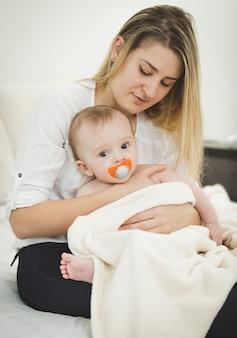 Gestemd portret van jonge zorgzame moeder die op bed zit en baby op handen houdt
