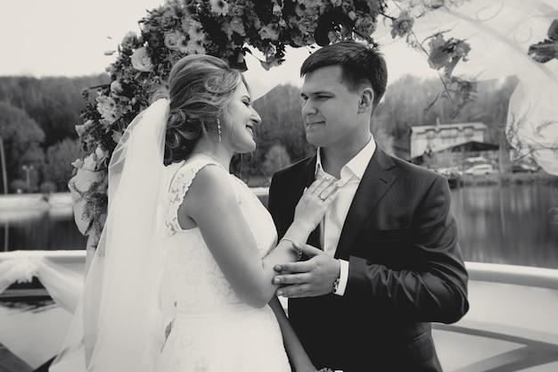Gestemd zwart-wit portret van gelukkige bruid en bruidegom die elkaar onder arch . bekijken