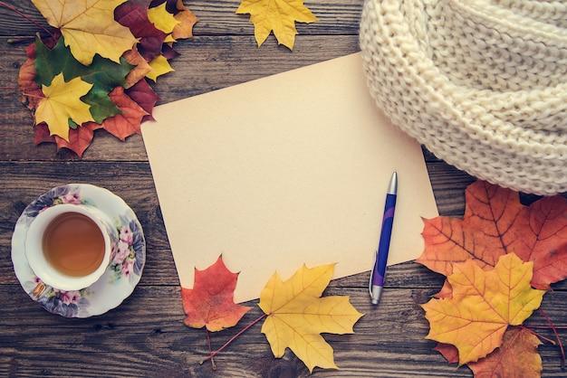 Gestemde foto met herfstbladeren, een kopje thee en een notebook