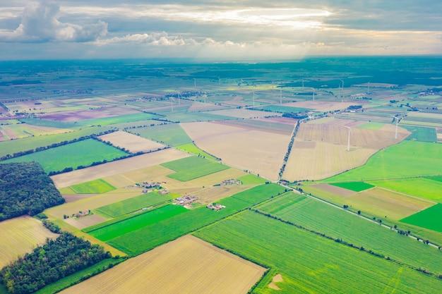 Gestikt panorprachtig uitzicht vanaf grote hoogte op kleurrijke velden, tegen de achtergrond van de zomerblauwe lucht, zomerlandschap met een drone, groene veldama