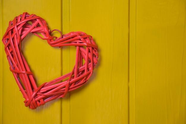Gestileerd hart van rode kleur van een geweven natuurlijk materiaal op een achtergrond van een houten geel bord. aan de rechterkant is er een plaats voor een inscriptie.