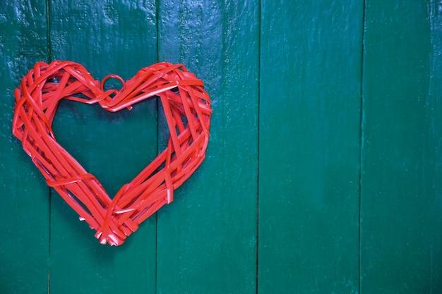 Gestileerd hart van rode kleur van een geweven natuurlijk materiaal op een achtergrond van een houten groen bord. aan de rechterkant is er een plaats voor een inscriptie.