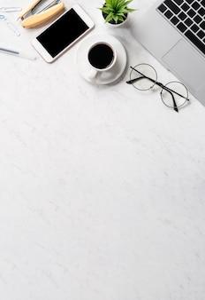 Gestileerd marmeren bureau met smartphone, laptop, glazen en koffie
