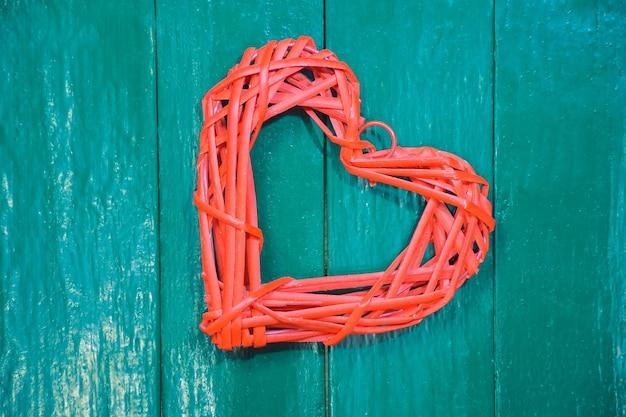 Gestileerd rood hart gemaakt van geweven natuurlijk materiaal op een achtergrond van een houten groen bord. gefotografeerd close-up