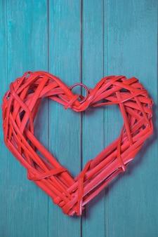 Gestileerd rood hart gemaakt van geweven natuurlijk materiaal op een verticale turquoise achtergrond close-up.