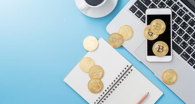 Gestileerd schoon blauw bureau met bitcoin, smartphone, laptop en koffiekop