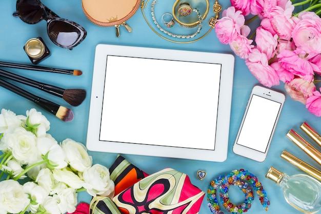 Gestileerd vrouwelijk bureaublad - vrouwenmodeartikelen op blauwe houten achtergrond, kopie ruimte op tablet- en telefoonscherm